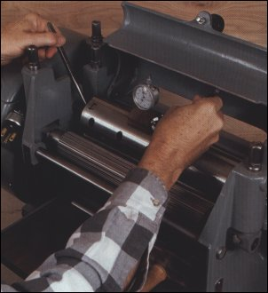 Gauge helps to anticipate knife shift - Using the planer cutterhead as a reference, Vaughan reads the gauge over each setscrew to know whether to raise or lower the knives and to anticipate how much each of the knives will shift during tightening.