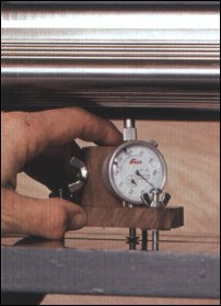 The planer bead gauge has to work in different positions. The base screw can straddle the bed slots. To check the feed rollers, orient the dial indicator, so it can take overhead reading. To check the bed rollers (shown here), flip the indicator on the tool post, sticking the plunger down through the hole in the base.