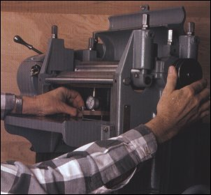 The bed gauge checks infeed and outfeed components. It also shows if bed adjustments are needed. By turning the pulley, the author rocks the cutterhead to be sure that he is reading bottom dead center of the arc of the knives.